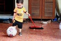 Dziecko z piłką i miotłą